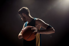 Silhouette view of a basketball player holding basket ball on black background Royalty Free Stock Images