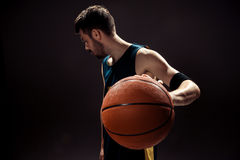 Silhouette view of a basketball player holding basket ball on black background Stock Photography