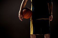 Silhouette view of a basketball player holding basket ball on black background Stock Photo