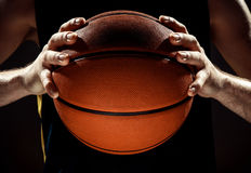 Silhouette view of a basketball player holding basket ball on black background. The silhouette view of a basketball player holding basket ball on black Stock Image
