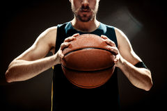 Silhouette view of a basketball player holding basket ball on black background Stock Images