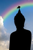 Silhouette view of bird on Buddha head statue with cloud background and rainbow Royalty Free Stock Photography