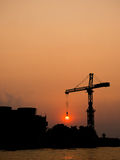 Silhouette view of construction crane hooking the twilight sun Royalty Free Stock Photo