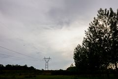 Silhouette view on electrical power line, tree and cloudy sky at Stock Photography