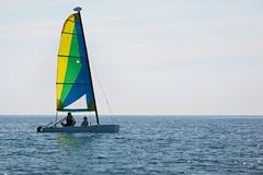 Family sailing at vacation. Silhouette view of family of two, father and son, and catamaran boat sailing in open sea, adventure vacation concept, copy space on Royalty Free Stock Images