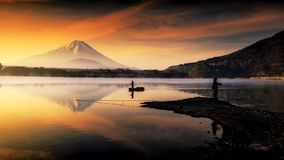 Silhouette Lake shoji with Fujisan at dawn. Silhouette view of fishermen on boat and edge at Shoji lake with mount Fuji view reflection at dawn with twilight sky stock images