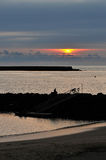 Silhouette view of jetty during a cloudy sunset Stock Image