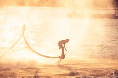 Silhouette and vintage color styl showing flyboard on Chaophya r Royalty Free Stock Images