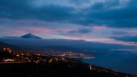 Silhouette of volcano del Teide surrounded by clouds in a nightly sky. Pico del Teide mountain in El Teide National park at night. Clouds enchant the Pico del royalty free stock images