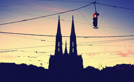 Silhouette of the Votive Church and stoplight at dusk. Silhouette of the Votive Church Votivkirche and suspended stoplight at dusk, color toning applied royalty free stock image