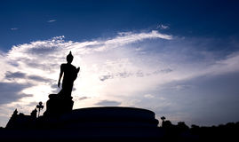 Silhouette walking buddha statue with blue sky Stock Photo