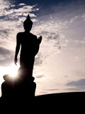 Silhouette walking buddha statue with sunlight flare Stock Photos