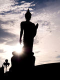 Silhouette walking buddha statue with sunlight flare Royalty Free Stock Photo