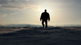 Silhouette walking in deep snow stock footage