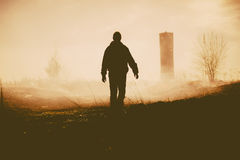 Silhouette of the walking person and tower. Stock Photography