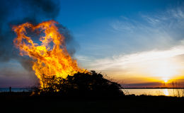 Silhouette of Walpurgis Night by the sea. Bonfire silhouette on Walpurgis Night by the sea and sunset by the horizon stock image