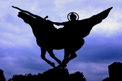 Silhouette of Warrior Statue with Sword. A silhouette of warrior statue with a sword and a moody cloudy blue background Stock Image