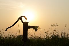 The silhouette water pump on the grass and rice field with the s Royalty Free Stock Photos