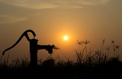 The silhouette water pump on the grass and rice field with the s Royalty Free Stock Image