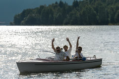 Waving men sitting in motorboat back lit Stock Image