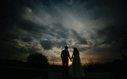 Silhouette of  wedding couple in field Stock Photo