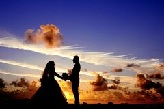 Silhouette of Wedding Couple Holding Hands Under Cloudy Blue Sky Royalty Free Stock Image