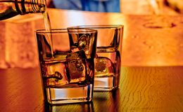 Silhouette of whiskey glasses with ice on bar table on warm atmosphere Royalty Free Stock Photo