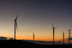 Silhouette wind generators turbines on sunset summer landscape i Royalty Free Stock Photo