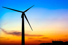 Silhouette wind turbine generator with factory emissions of carb Stock Images
