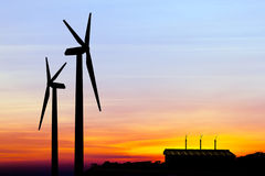 Silhouette wind turbine generator with factory emissions of carb Royalty Free Stock Images