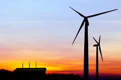 Silhouette wind turbine generator with factory emissions of carb Royalty Free Stock Photography
