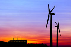 Silhouette wind turbine generator with factory emissions of carb Royalty Free Stock Image