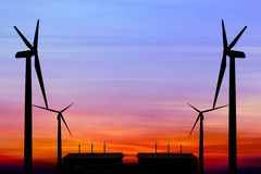Silhouette wind turbine generator with factory emissions of carb Royalty Free Stock Photos