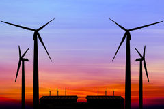 Silhouette wind turbine generator with factory emissions of carb Stock Photography