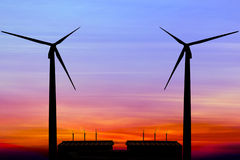 Silhouette wind turbine generator with factory emissions of carb Stock Photo