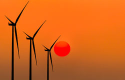 Silhouette wind turbines generating electricity Stock Photos
