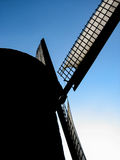 Silhouette of windmill blades against blue sky Stock Photos