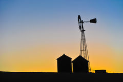 The silhouette of a windmill and buildings Stock Image