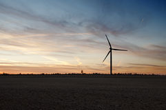 Silhouette of windmill generator at dusk. Silhouette of windmill generator in the fields at dusk Stock Image