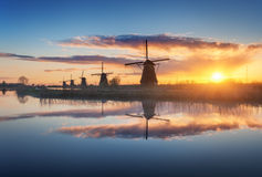 Silhouette of windmills at sunrise in Kinderdijk, Netherlands. Silhouette of windmills at amazing foggy sunrise in Kinderdijk, Netherlands. Rustic landscape with Stock Images