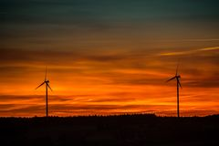 Silhouette of Windmills Under Orange Sunset Stock Image