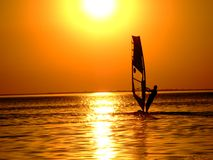 Silhouette of a windsurfer. On waves of a gulf on a sunset Stock Photography