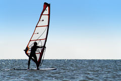 Silhouette of a windsurfer on the blue sea stock photos
