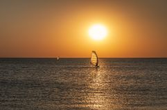 The silhouette of a windsurfer on a board under a sail moves along a calm water surface at sunset over the sea, horizon stock images