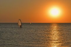 The silhouette of a windsurfer on a board under a sail moves along a calm water surface at sunset over the sea, horizon royalty free stock photography