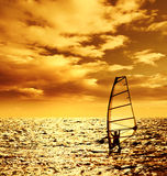 Silhouette windsurfer over sunset Stock Photos