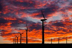 Silhouette of windturbines on an amazing sunset stock photography