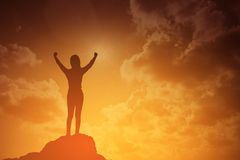 Silhouette of winning success woman at sunset or sunrise standing and raising up her hand in celebration.business success concept. Silhouette of winning success Stock Images