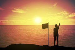 Silhouette of winning success woman at sunset or sunrise standing and raising up her hand near the flag in celebration. Of having reached mountain top summit Royalty Free Stock Photo