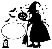 Silhouette of a witch holding Halloween pumpkin and empty speech bubble. Stock Photo
